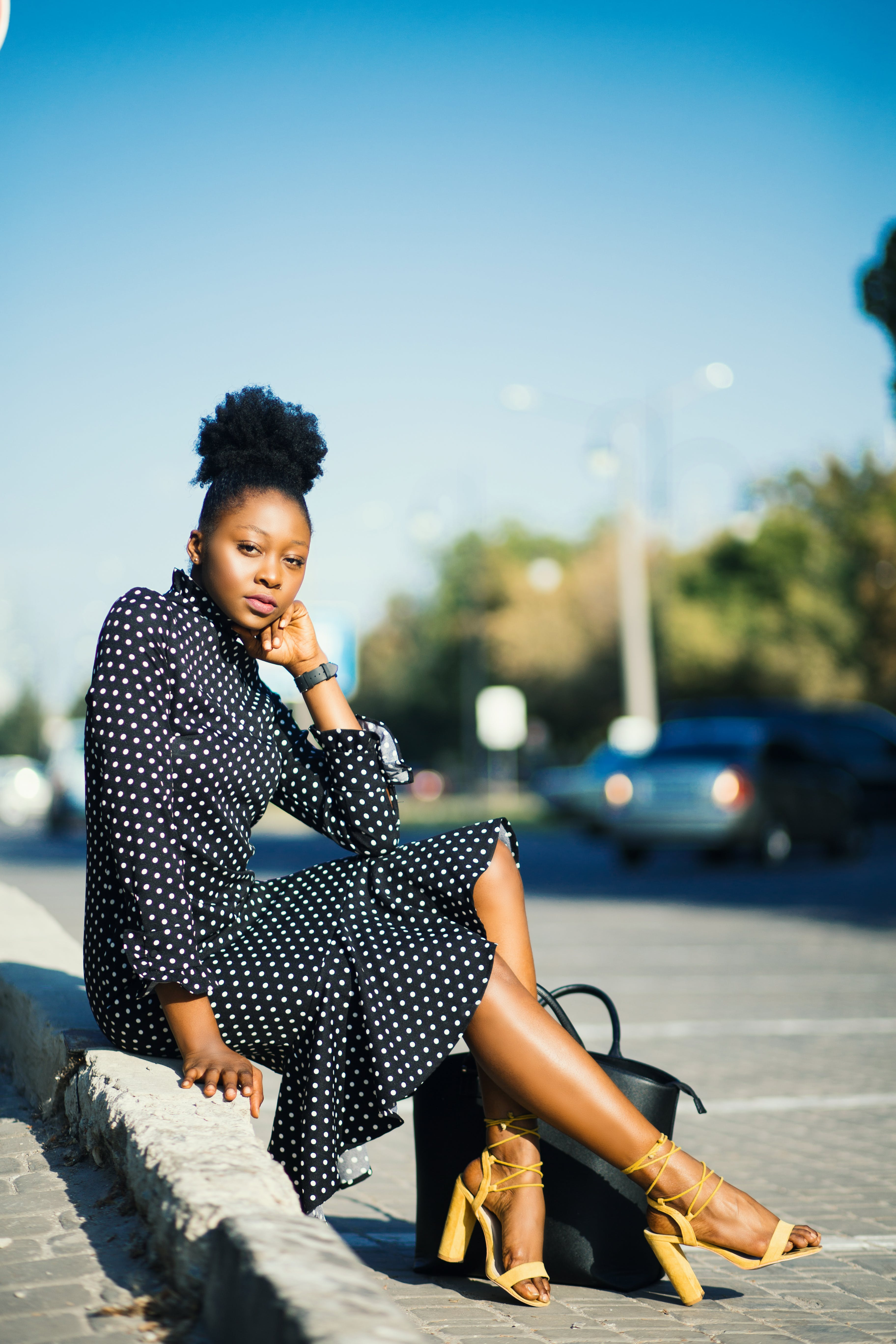 Woman in Black and White Polka-dot Dress Sitting Beside Pavement