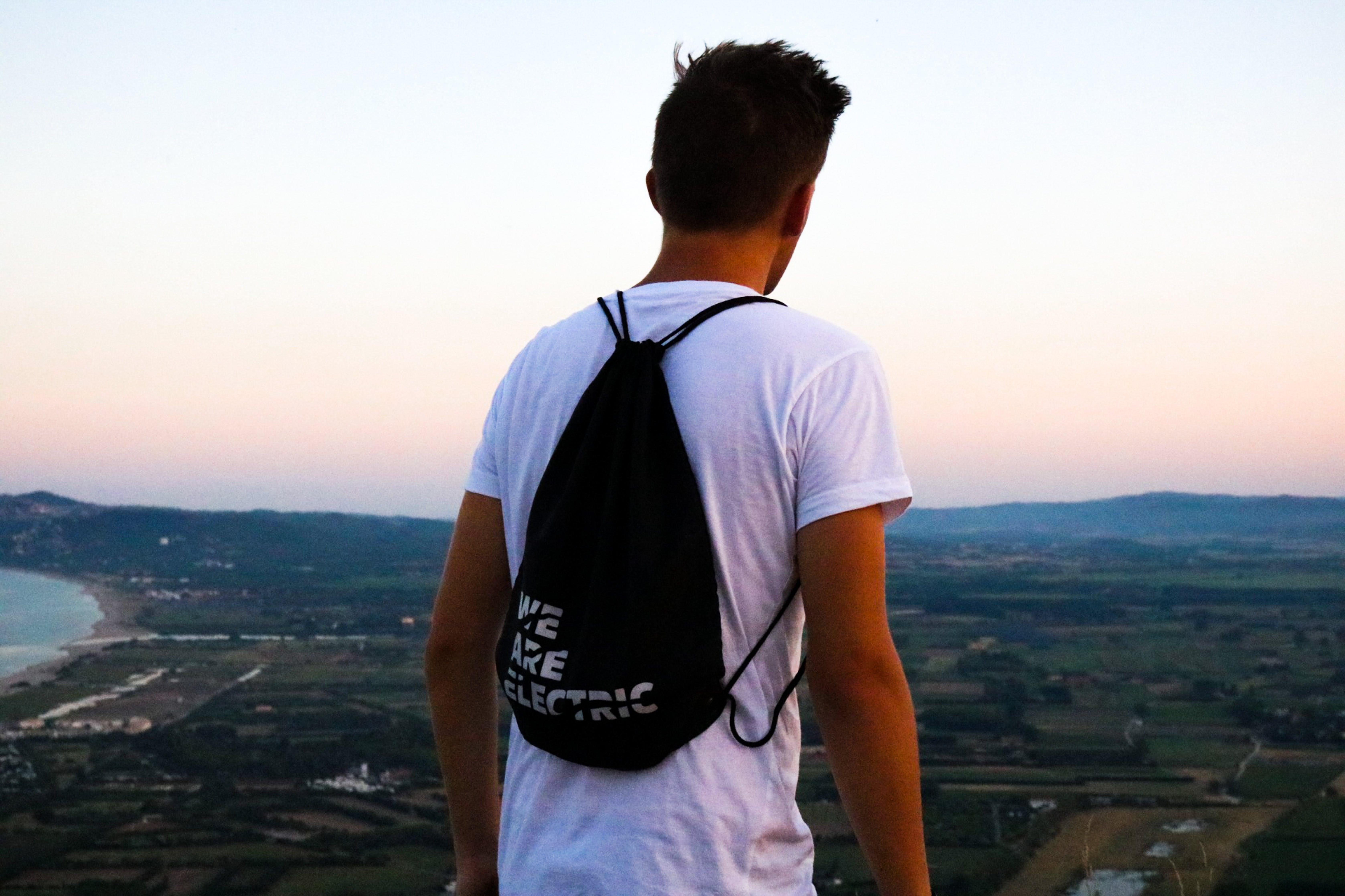 Man In White T-shirt With Black String Bag