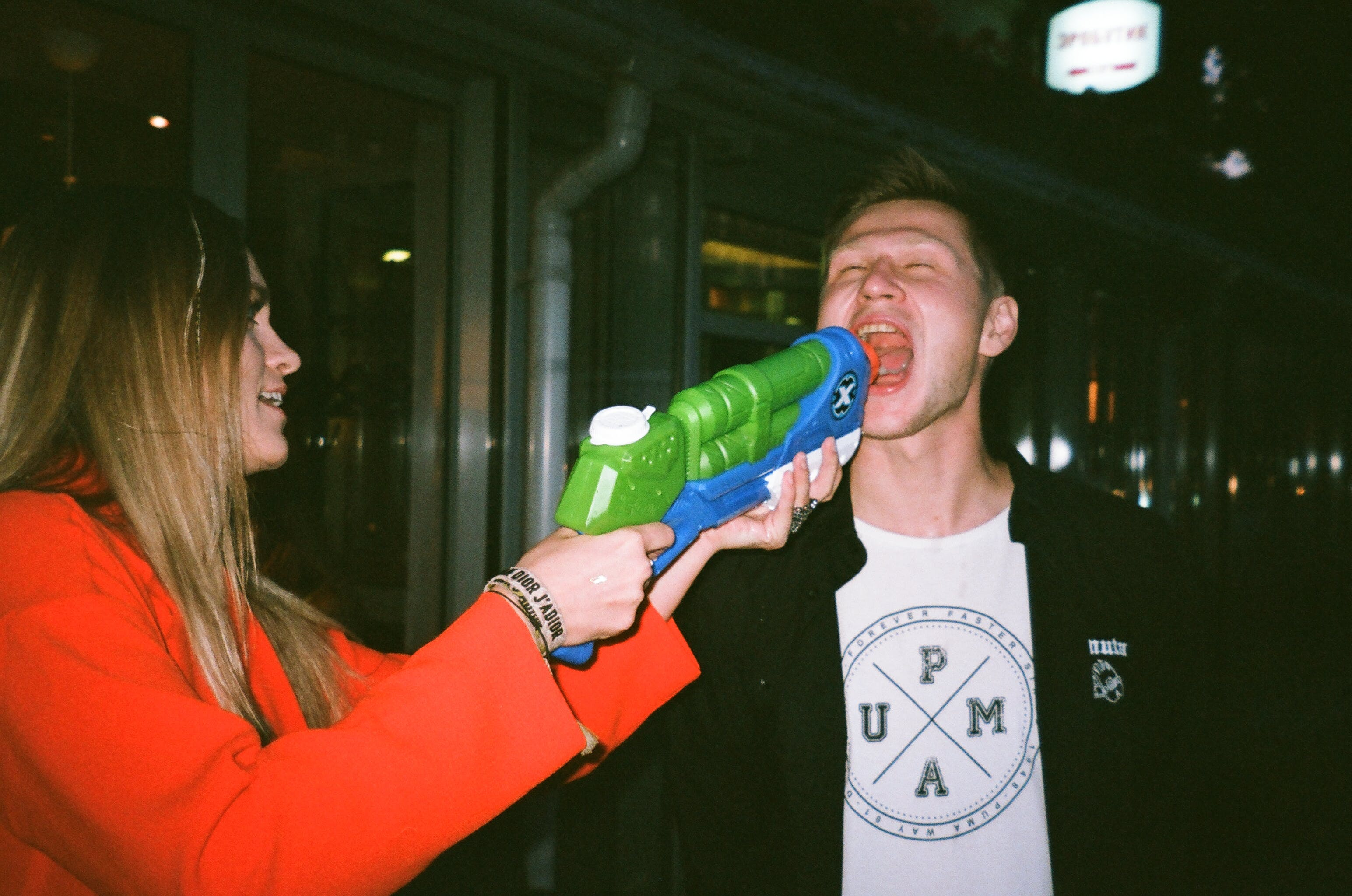 Woman Pointing Plastic Water Gun on Man's Mouth