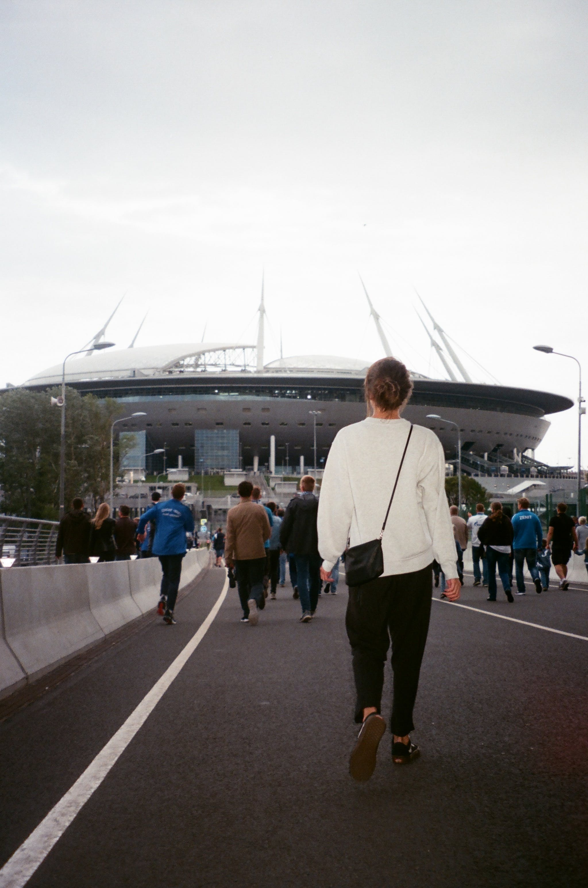 Woman in White Long-sleeve Top Walking to Stadium
