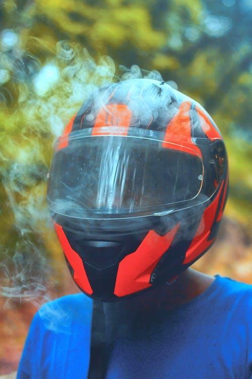 Person Wearing Orange and Black Full-face Helmet