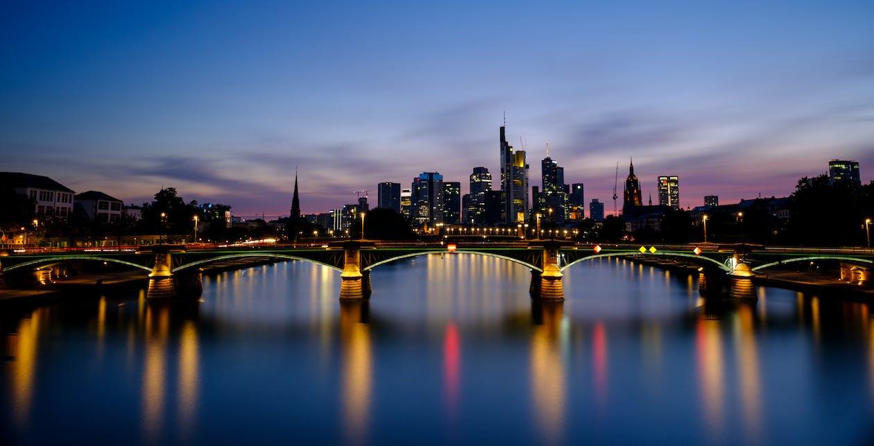 Bridge Across City Buildings during Nighttime