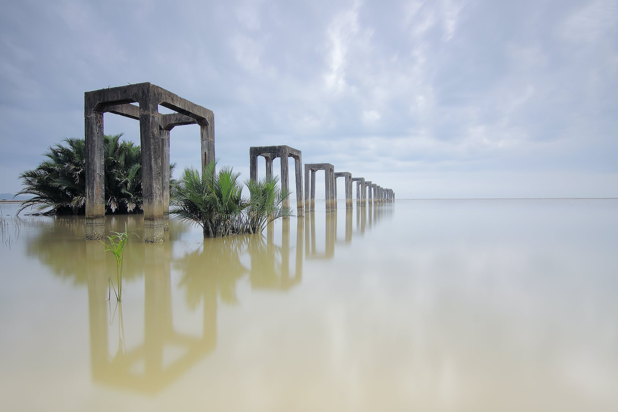 Gray Concrete Arches on Body of Water Under White Skies