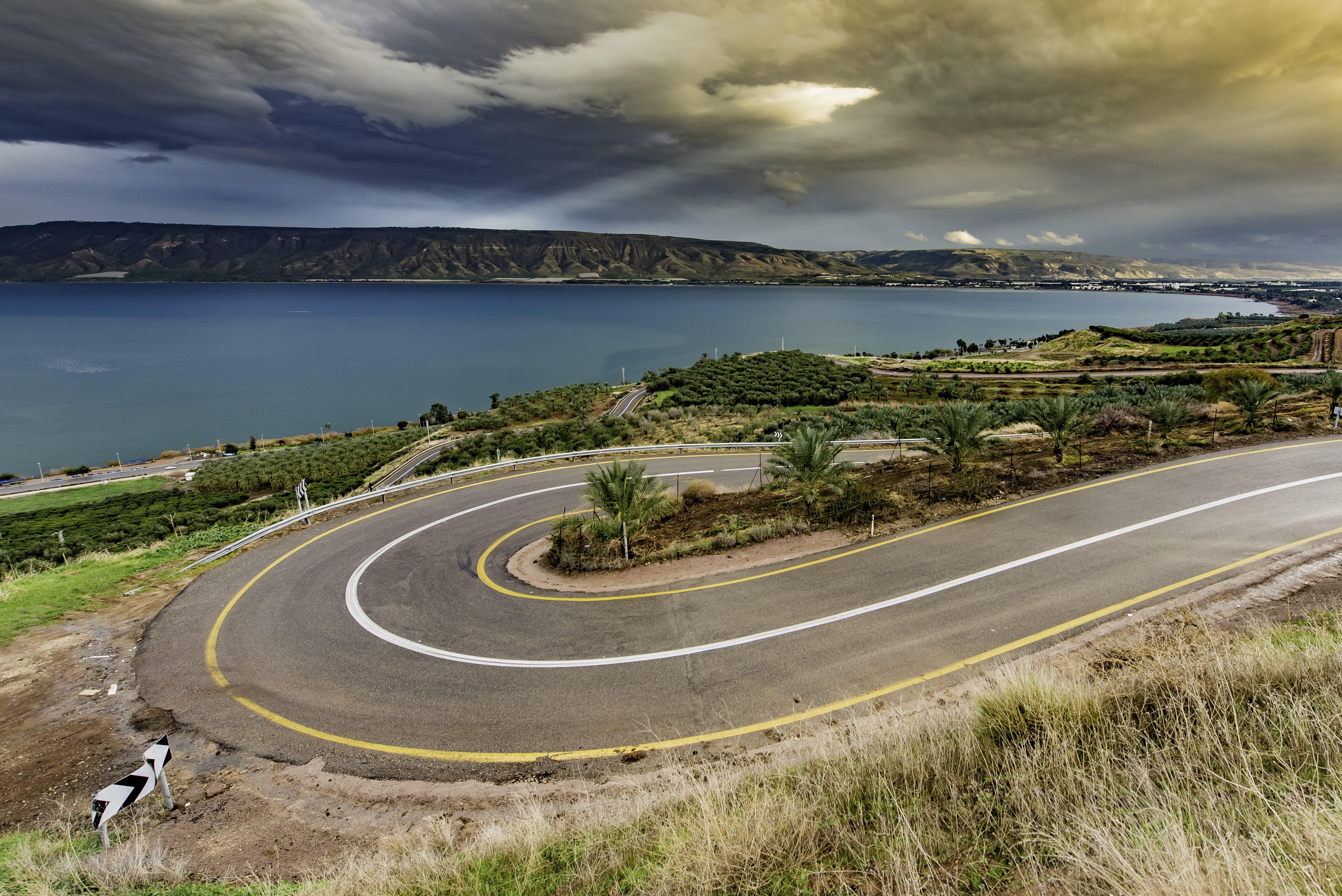 Curve Asphalt Road Near Blue Sea Under Gray Sky