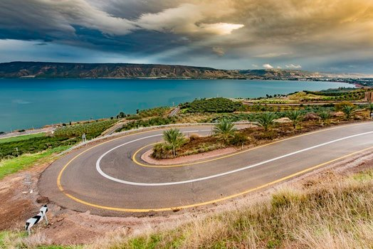 Curve Asphalt Road Near Blue Sea Under Gray Sky