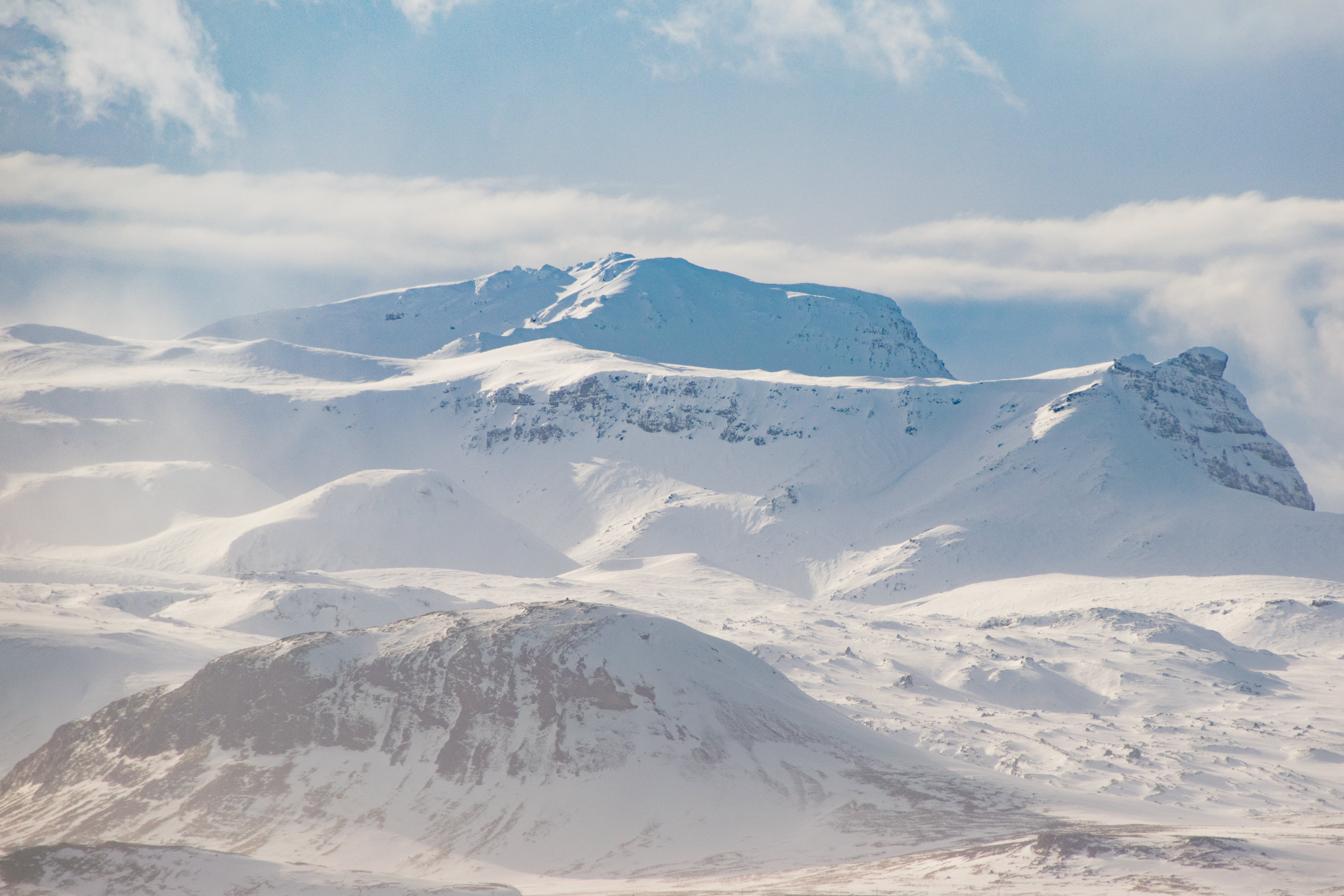 Snow Covered Mountain Ranges Under the White Skies