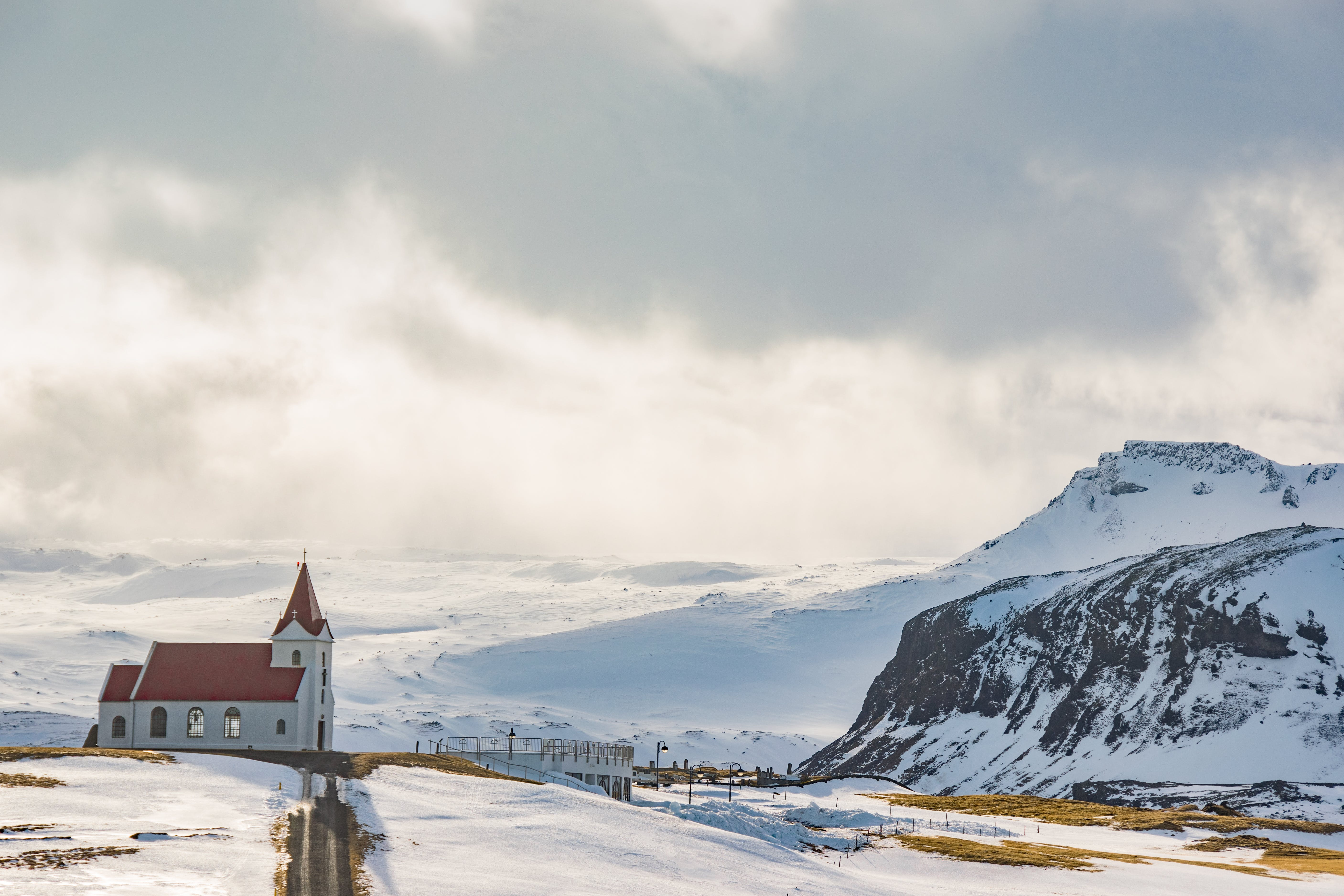 White Cathedral Near Mountain Covered With Snow