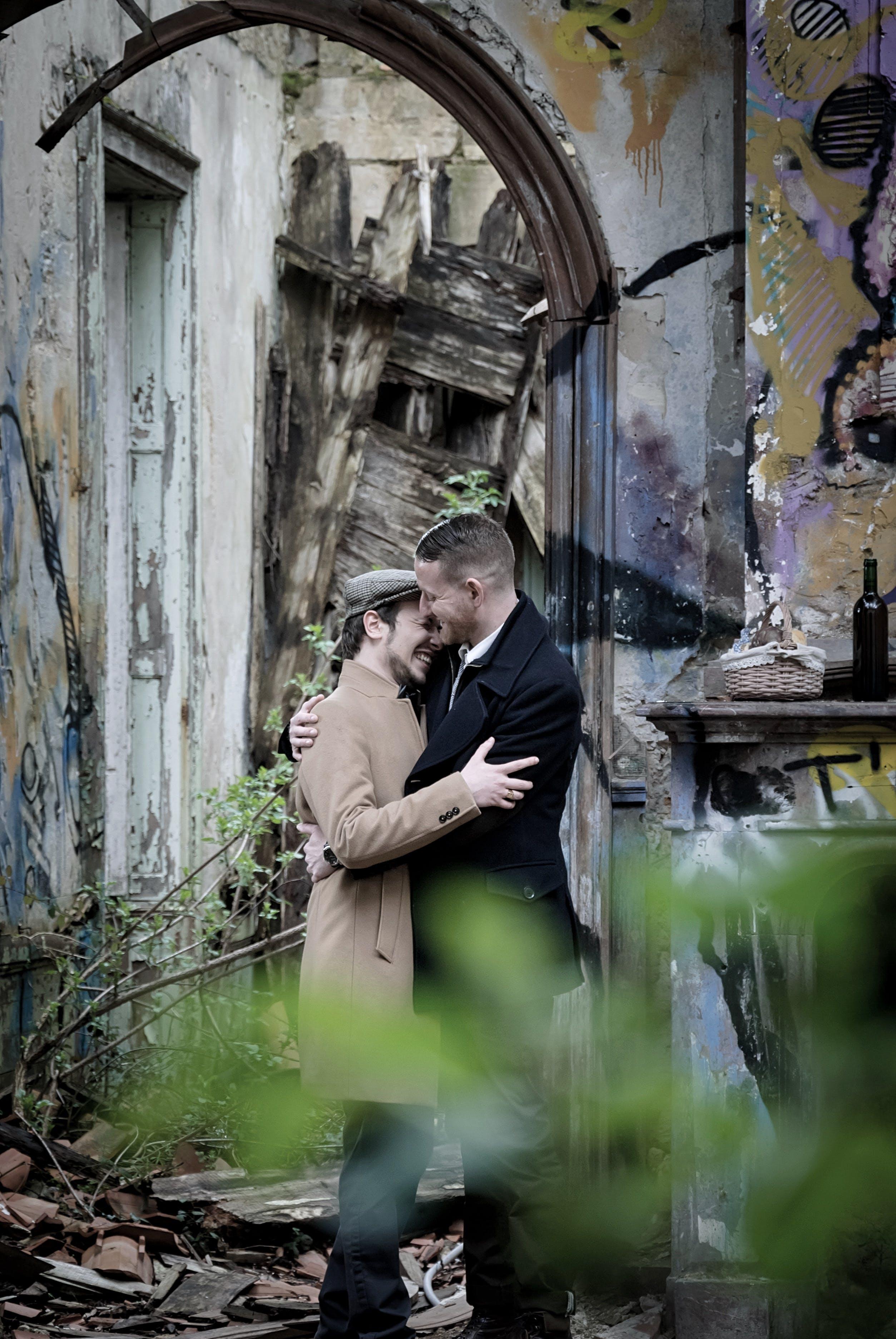 Man Embracing Man Near Gray Wall