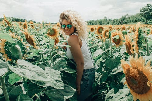 Woman in White Tank Top Standing in Sunflower Field
