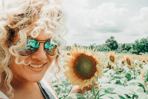 Smiling Woman Holding Sunflower