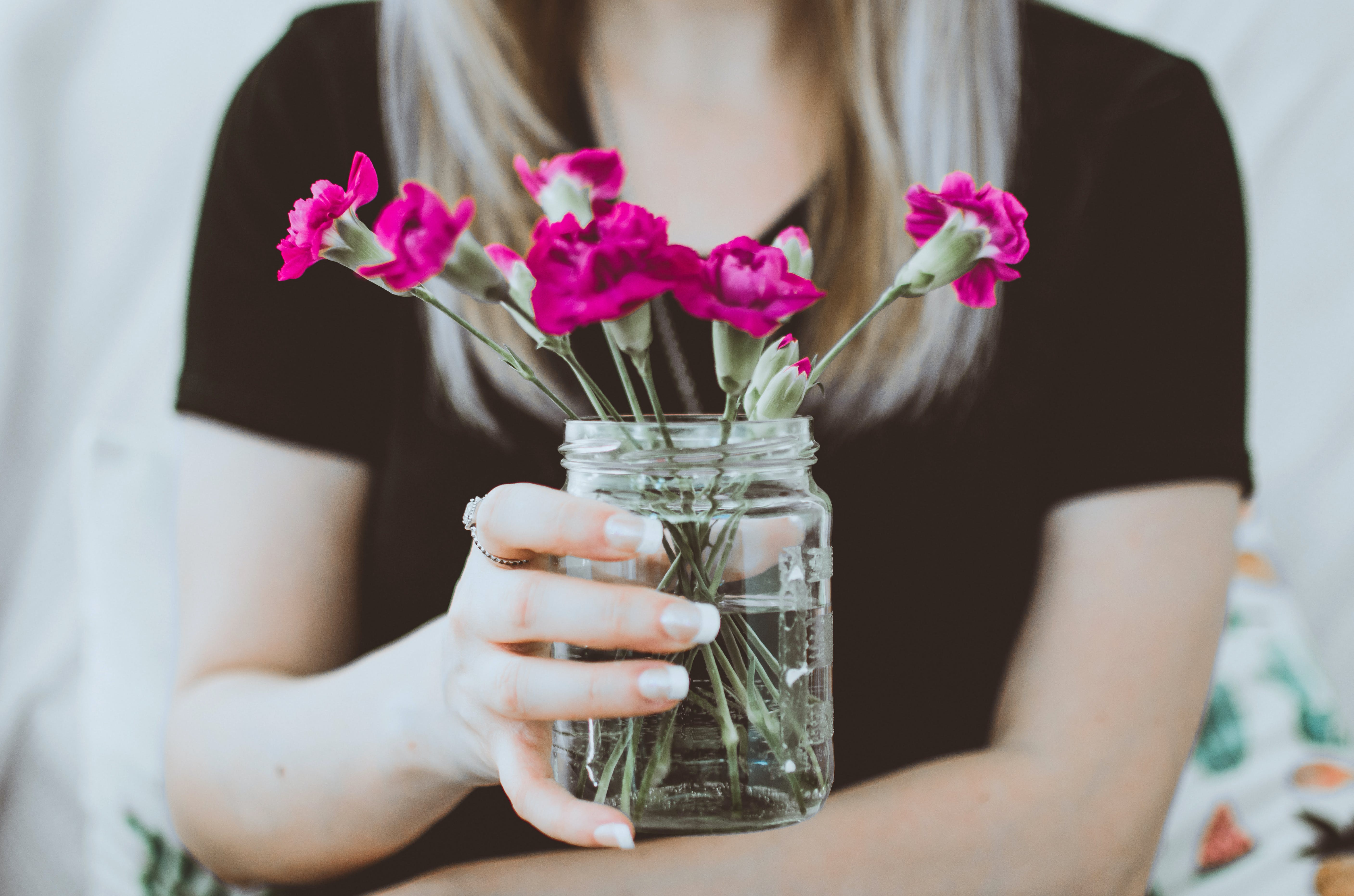 Person Holding Mason Jar With Purple Flowers Inside