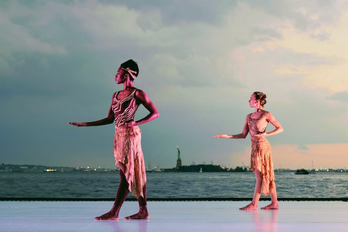 Two Women Posing Near Body of Water