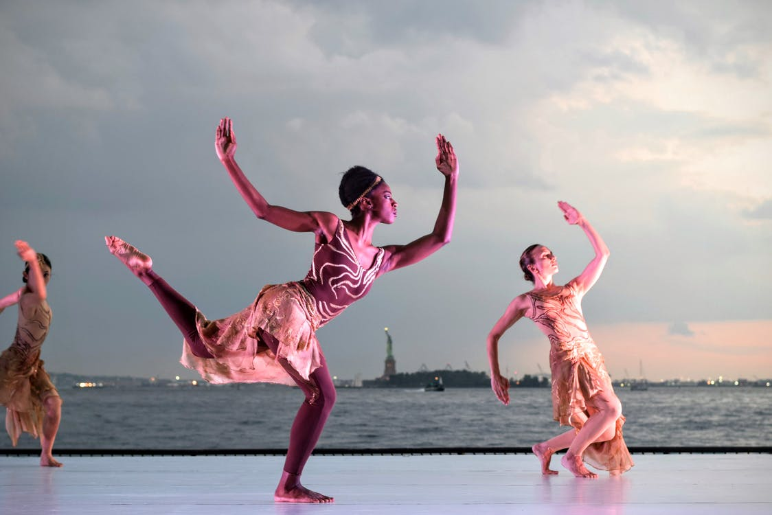 Three Women Dancing Near Body of Water