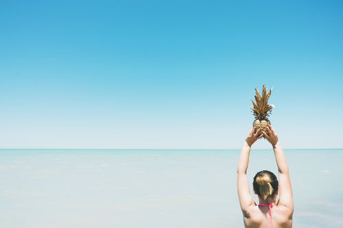 Woman Holding Pineapple Fruit Standing Near Body of Water