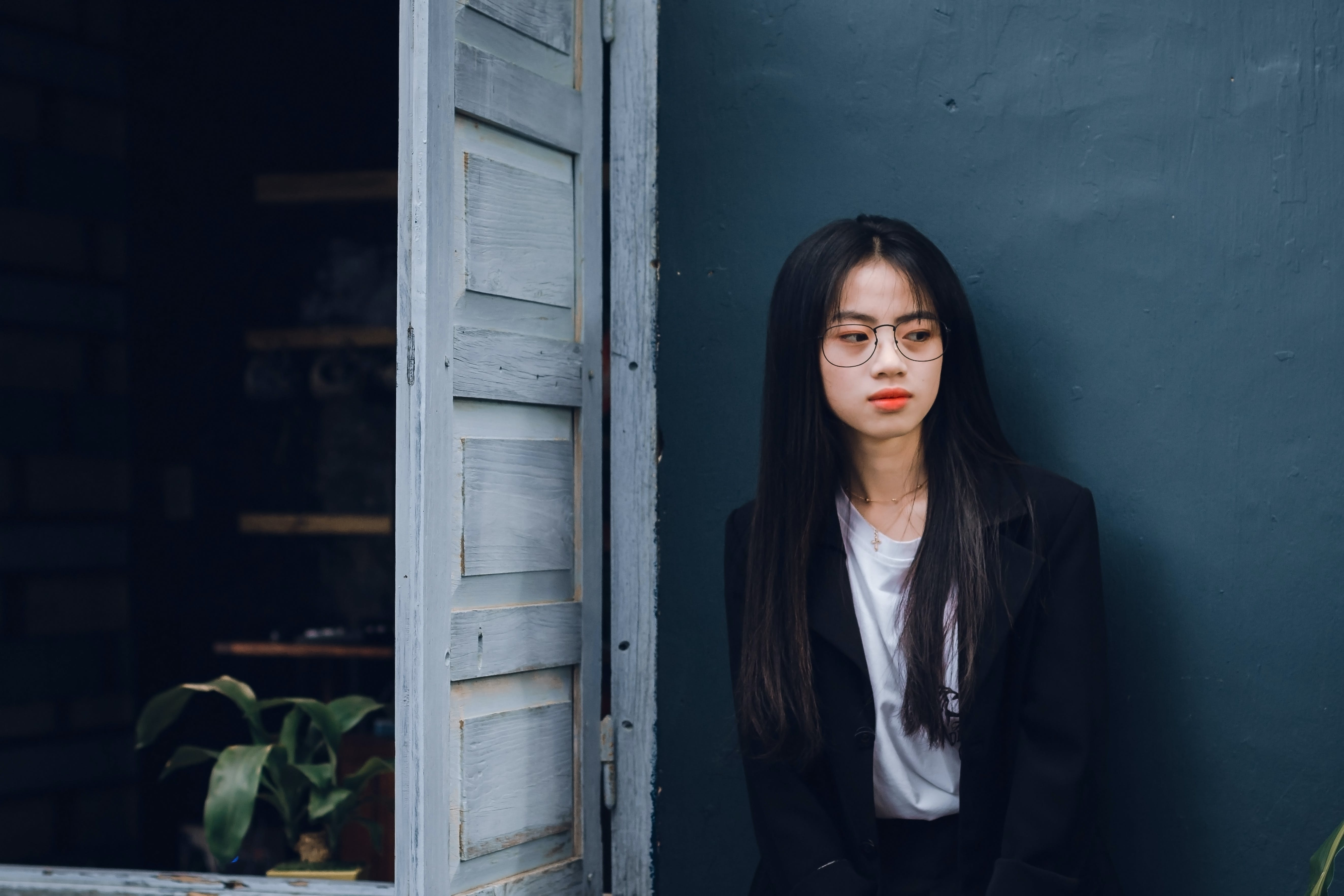 Woman Wearing Black Suit Near Brown Wooden Door