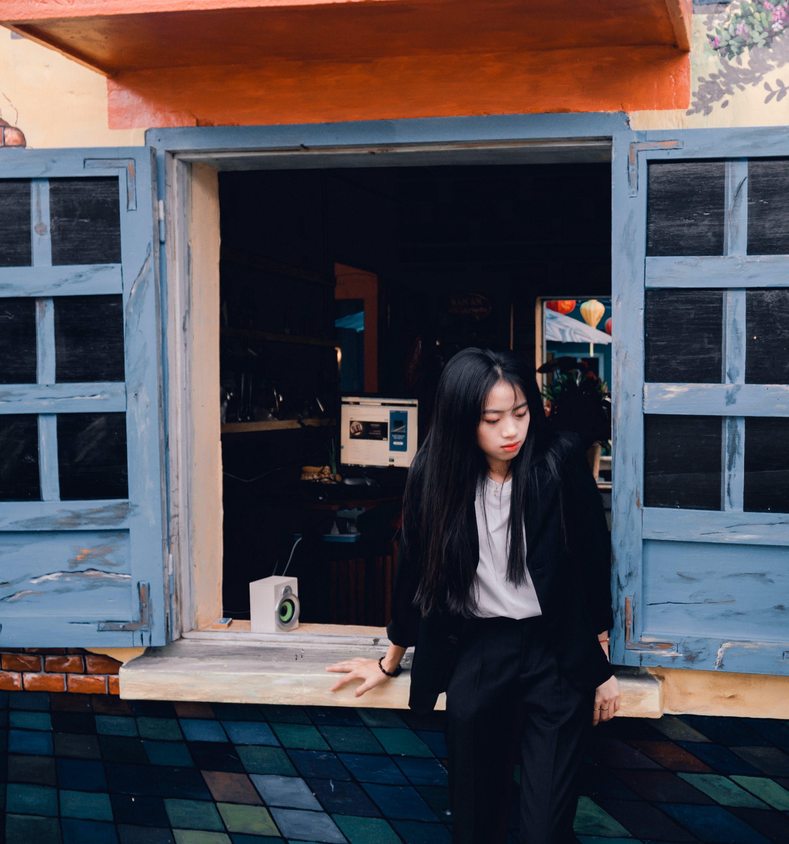 Woman Sitting on Brown Wooden Window