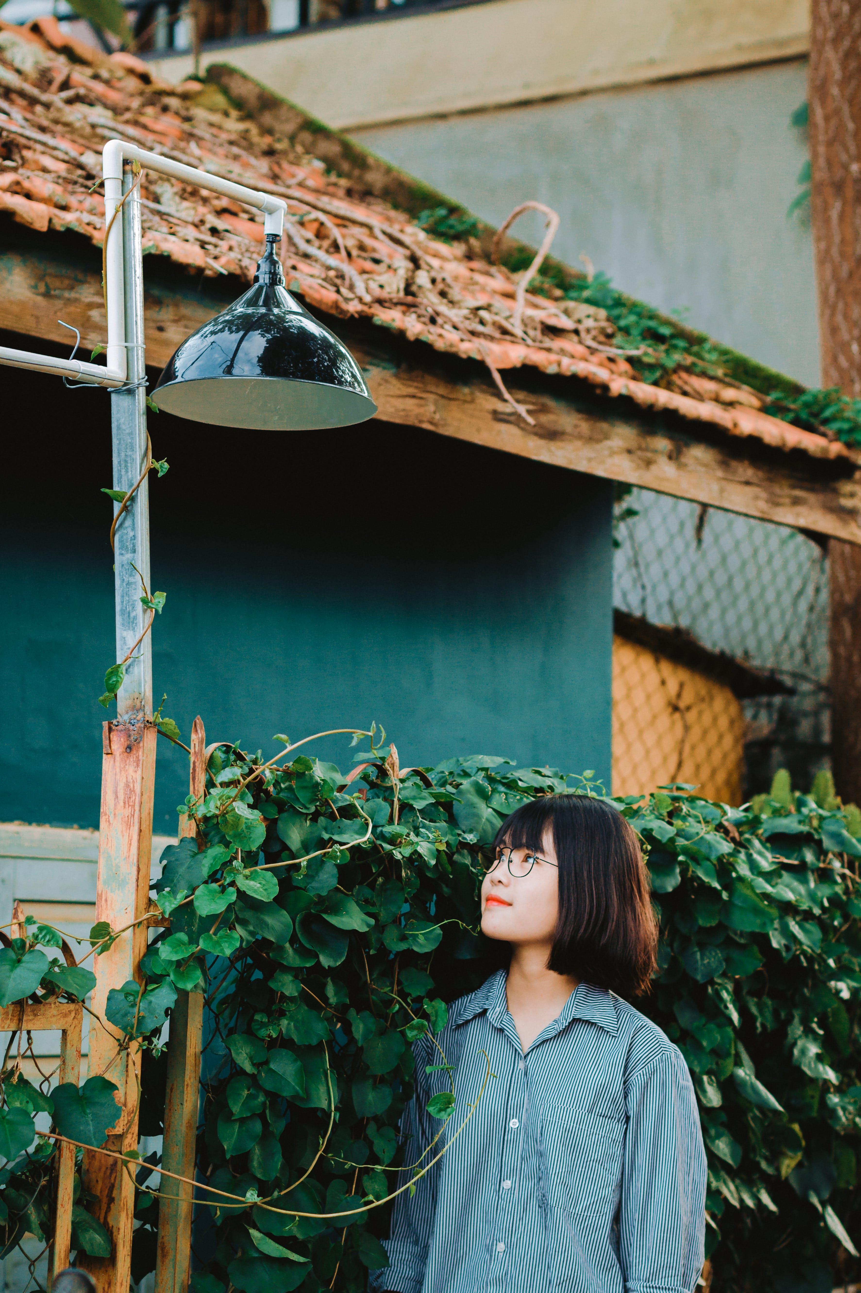 Woman Standing Underneath Pendant Lamp