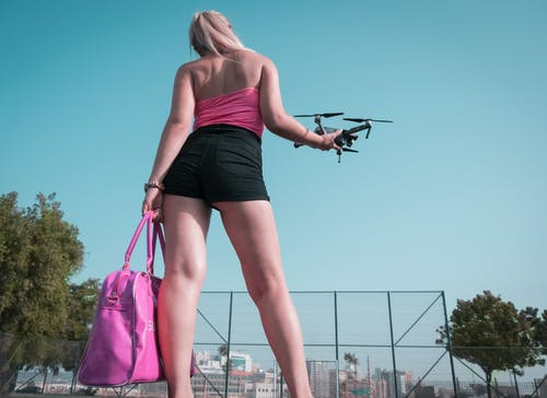 Woman Standing While Holding Quadcopter Drone