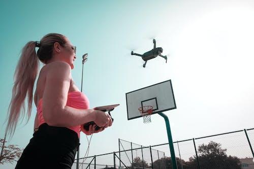 Woman Controlling Black Drone