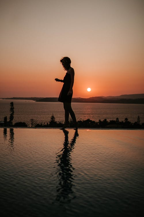 Silhouette Photography of Person Standing on Swimming Pool Edge