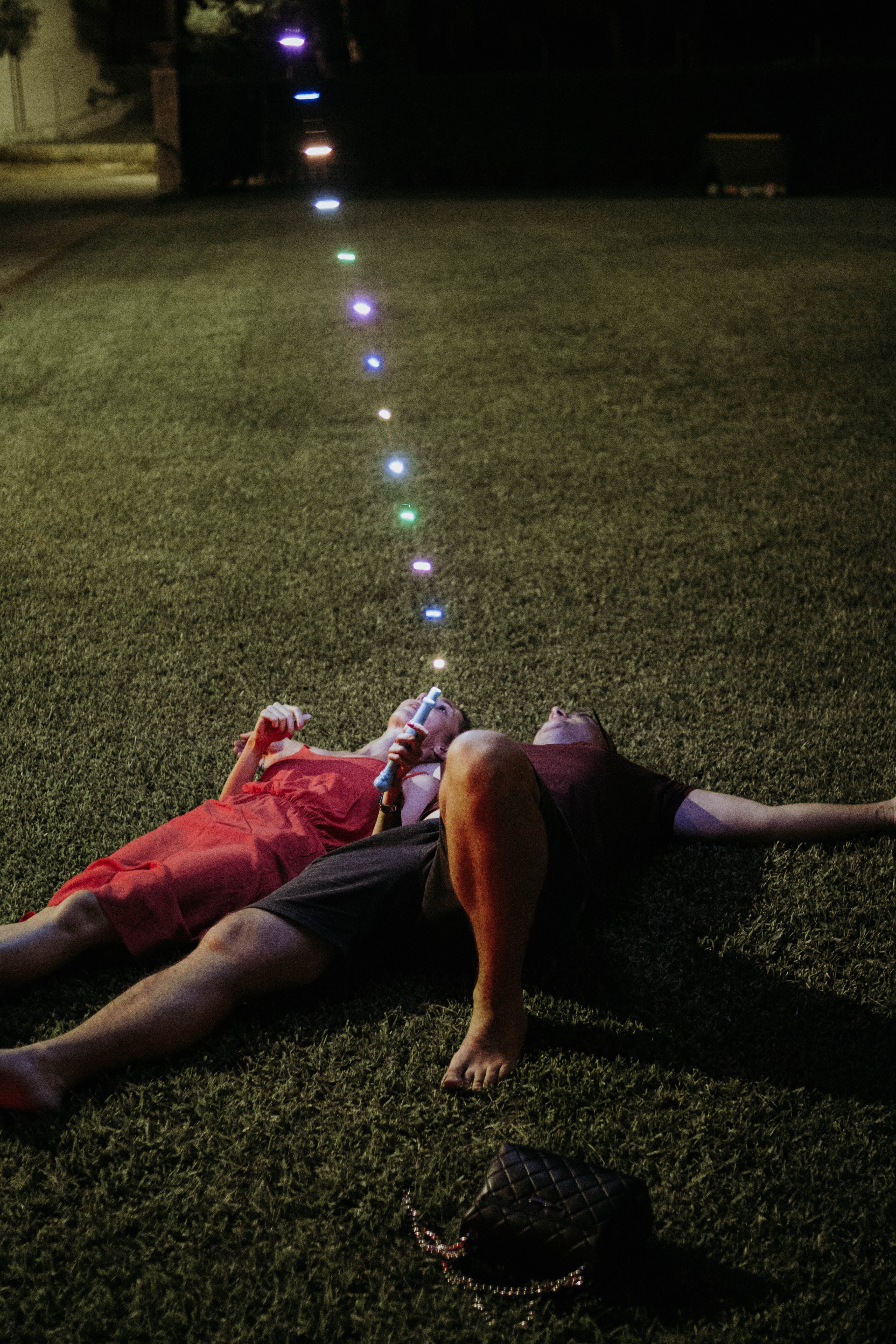 Man and Woman Lying on Green Grass Holding String Lights