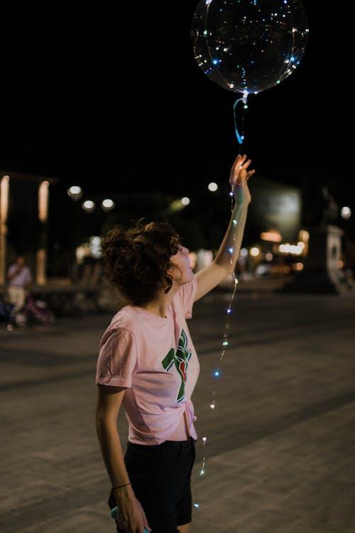 Woman Holding Lighted Balloon