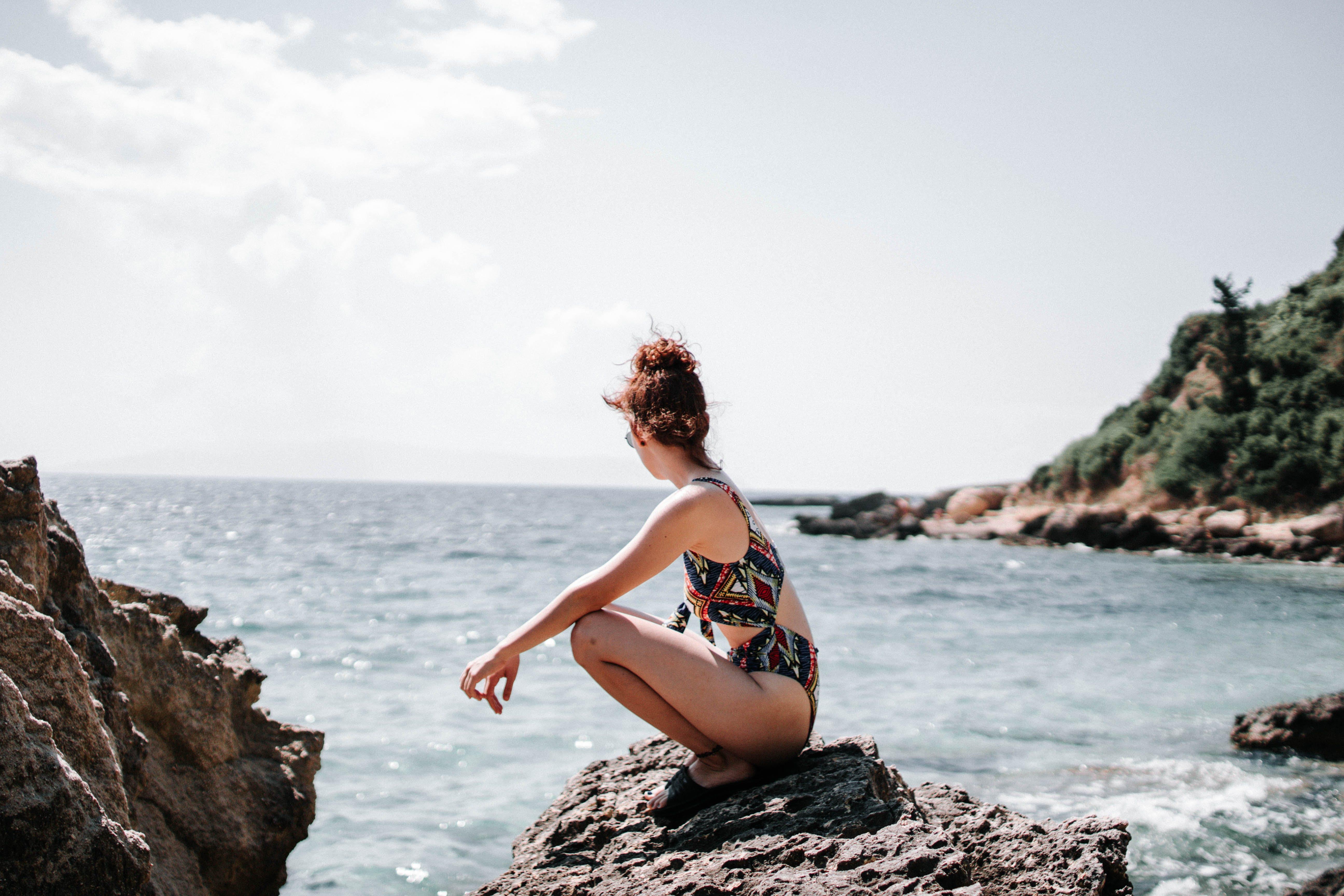 Woman in Swim Suit Sitting on a Rock