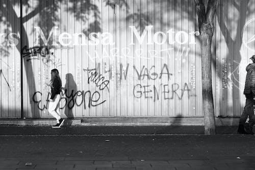 Grayscale Photo Of Woman Walking On Sidewalk