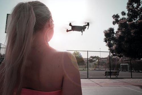 Woman Looking At Flying Drone