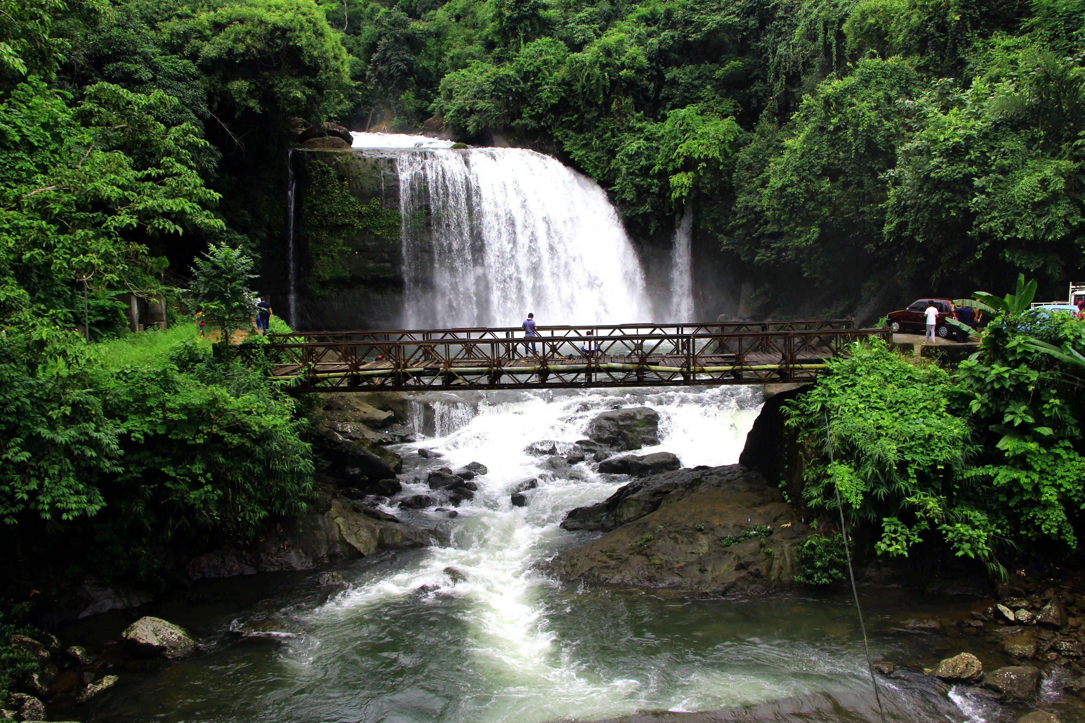 Person Standing on Bridge Near Waterfalls