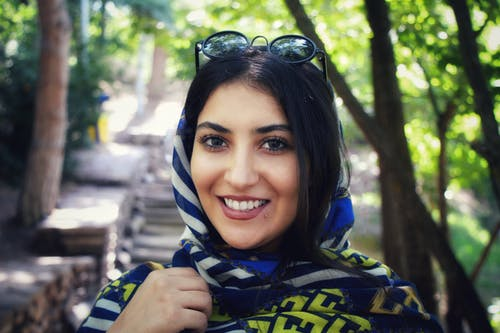 Smiling Woman Wearing Multicolored Headscarf and sunglasses Near Green Trees