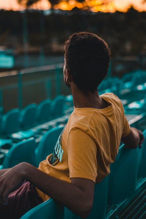 Gratis lagerfoto af mand, orange himmel, sidde, sløret baggrund