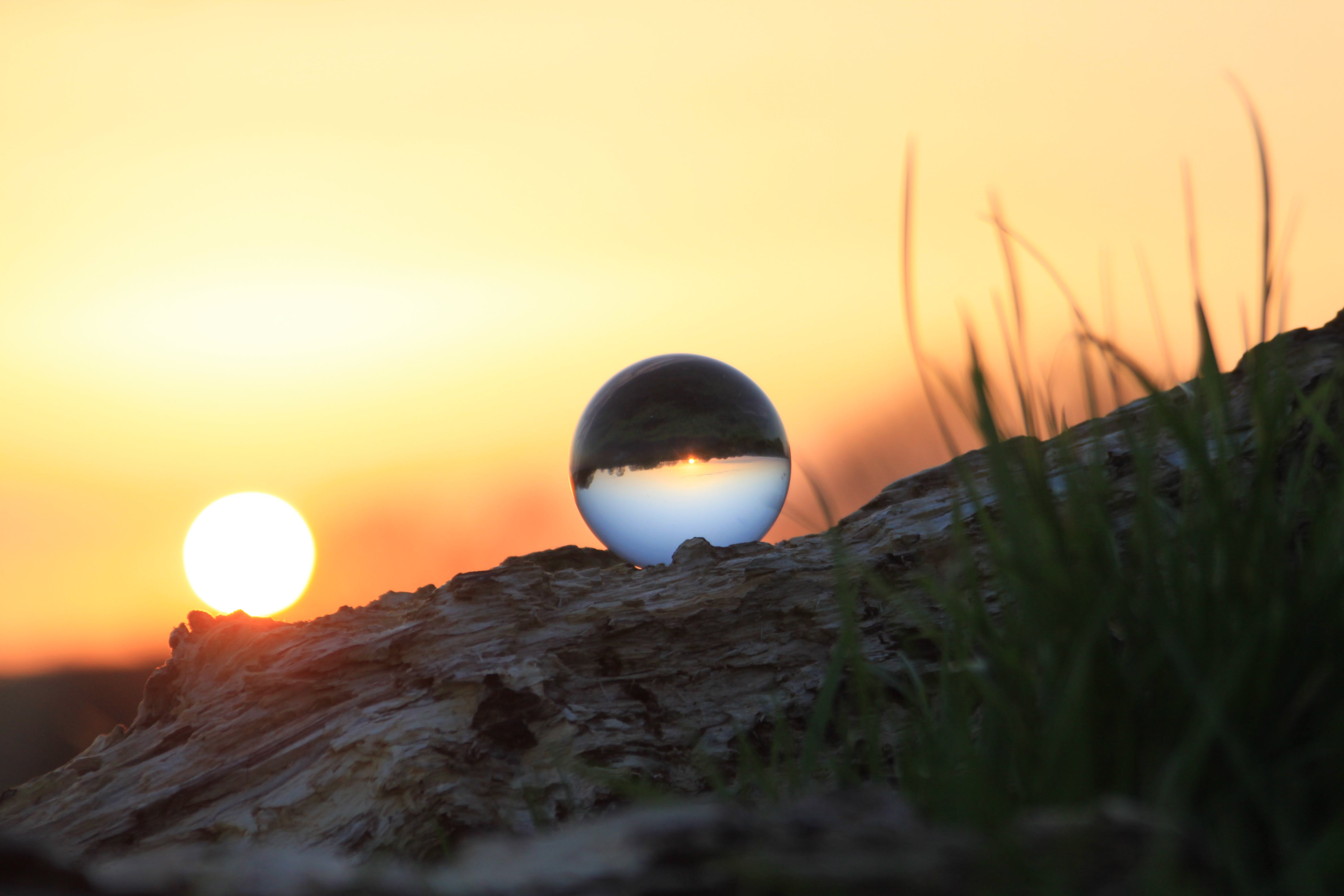 Photography of Glass Ball on Brown Rock Formation during Sunset