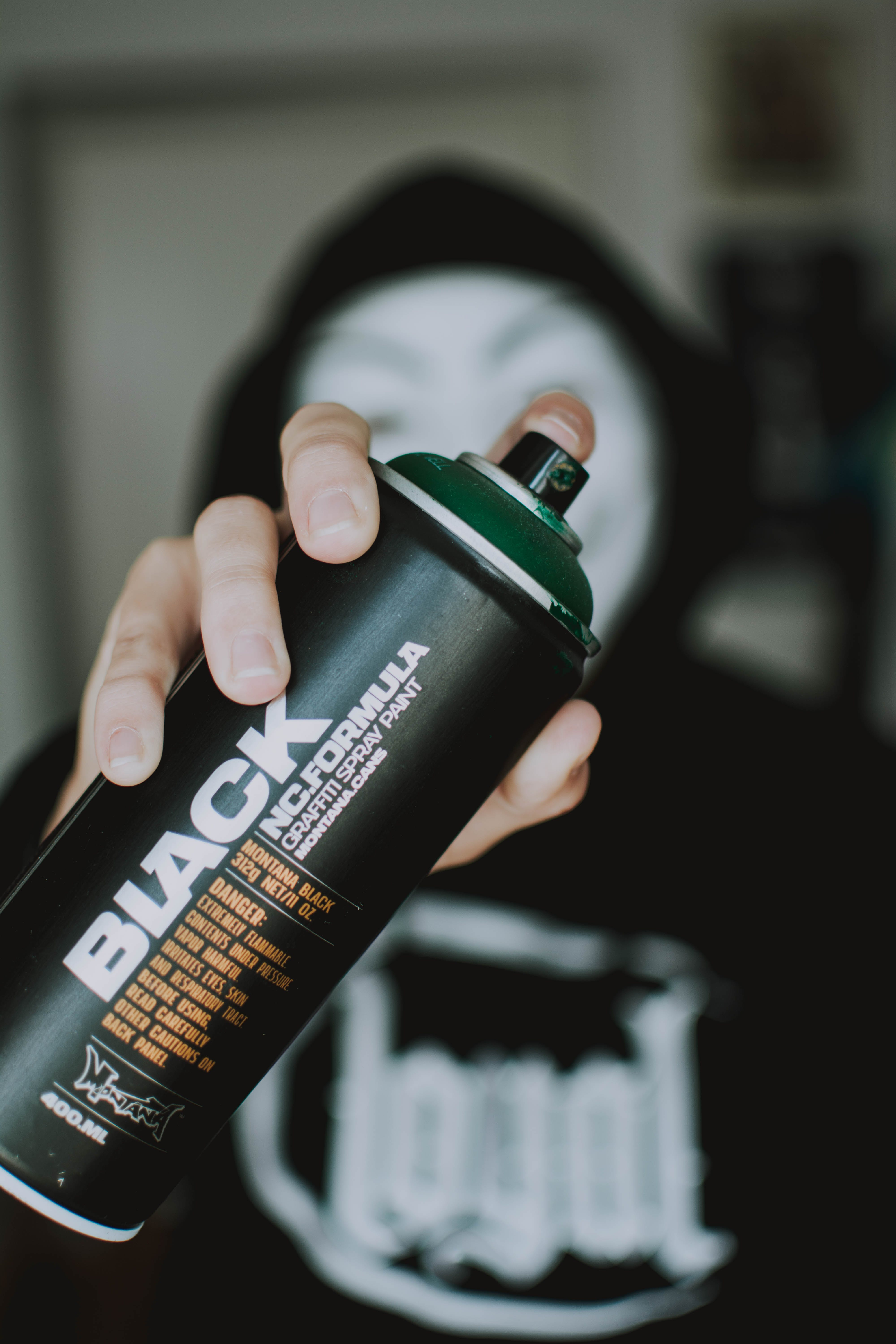 Person Holding Black Spray Bottle