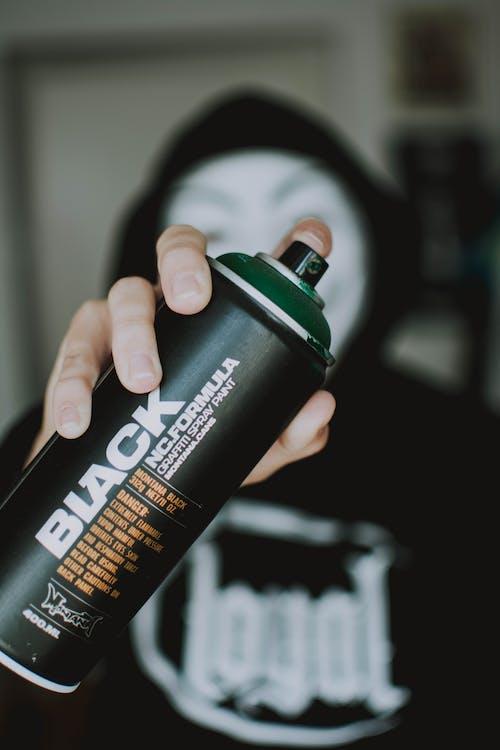 Person Holding Black Spray Bottle