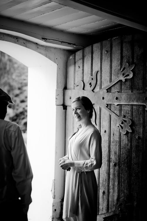 Grayscale Photography Of Woman Standing Beside Door