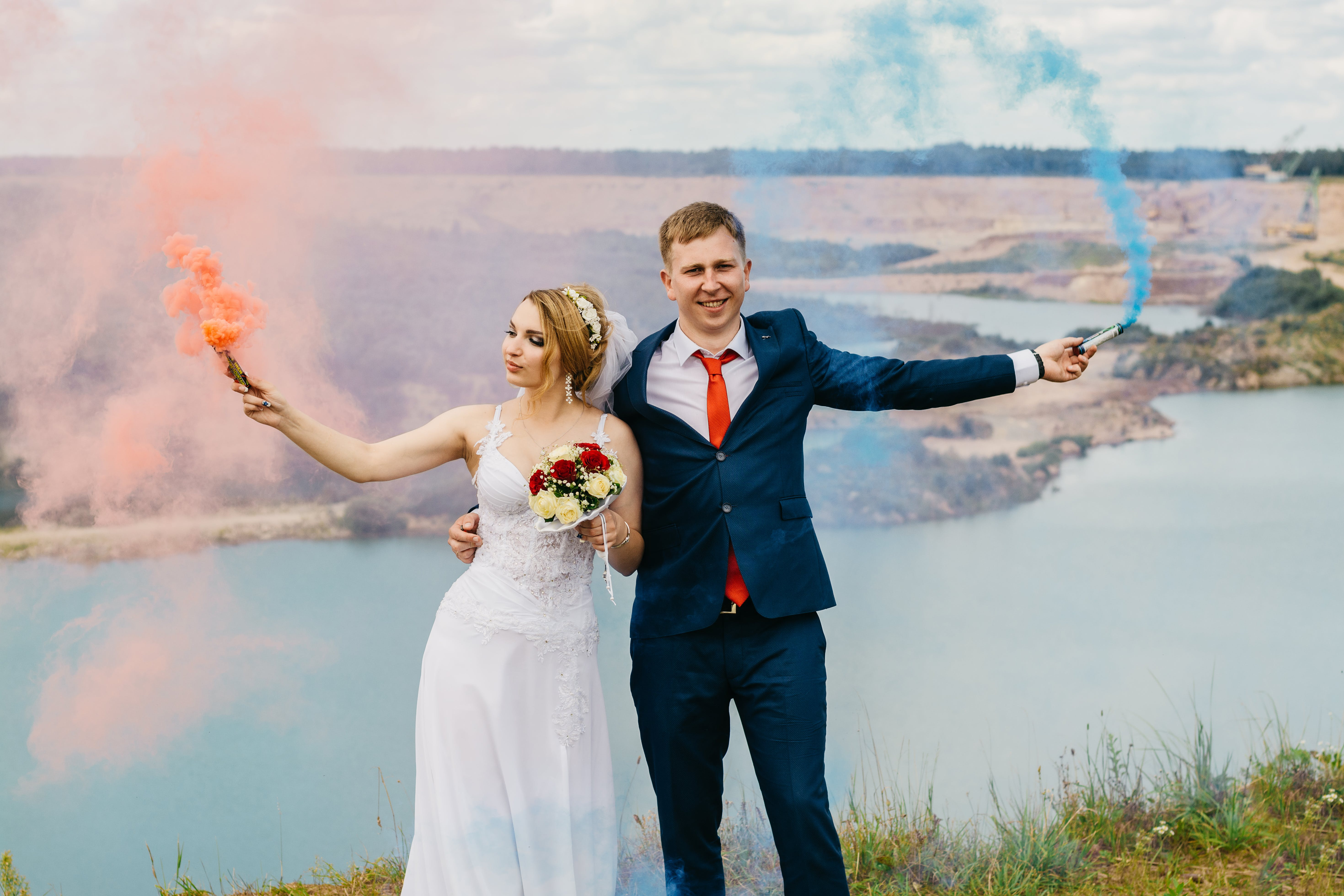 Bride And Groom Holding Smoke Bombs Near Body Of Water