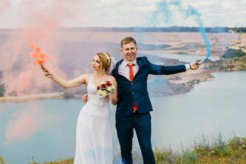 Braut Und Bräutigam Halten Rauchbomben Nahe Dem Gewässer