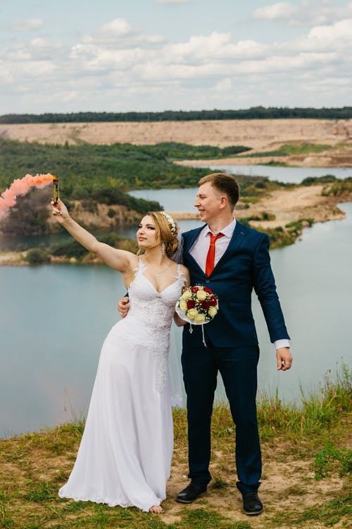 Couple Standing On Green Grass Near Body Of Water