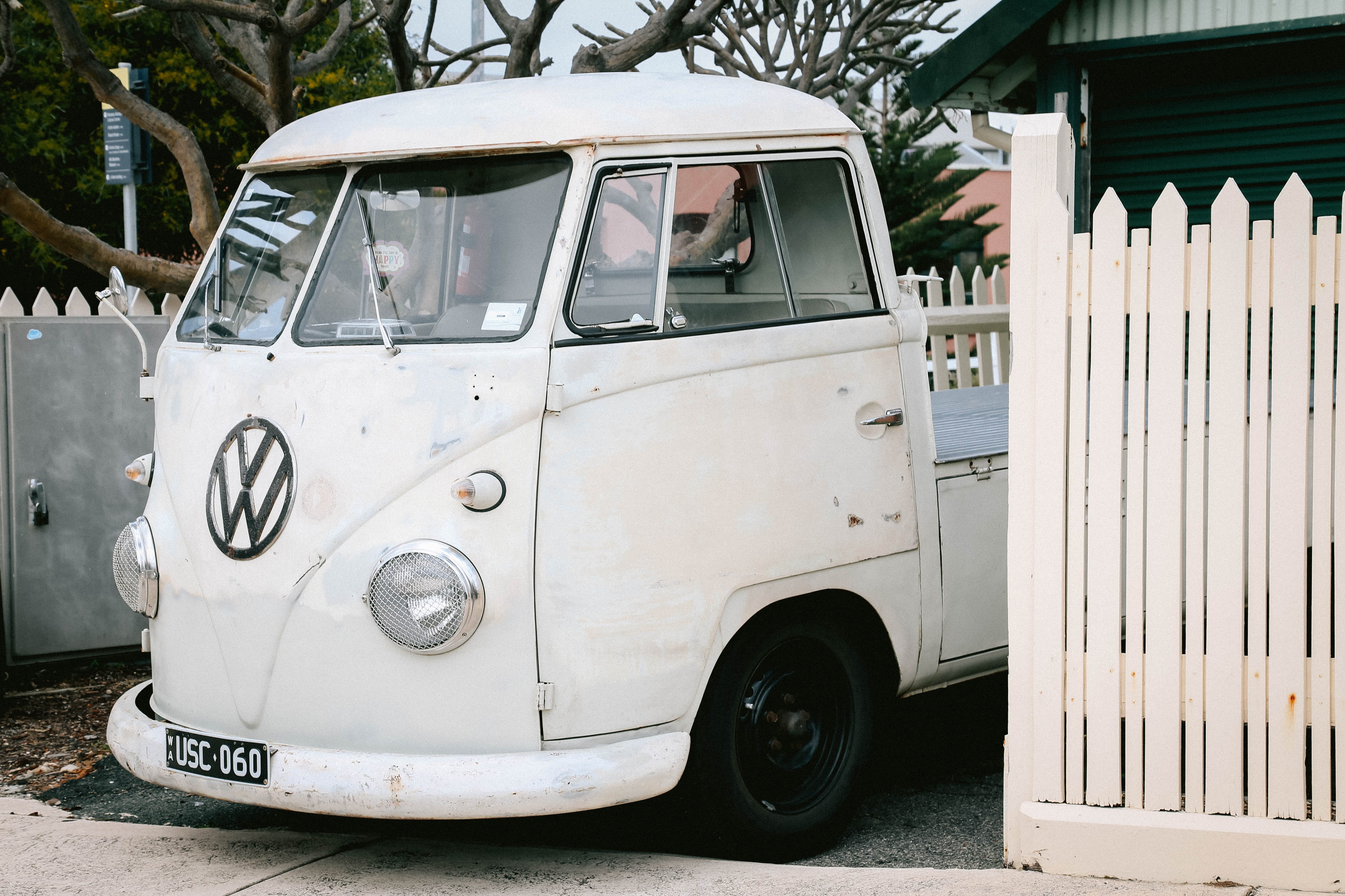 White Volkswagen Vehicle on Parking Lot Near White Wooden Picket Fence