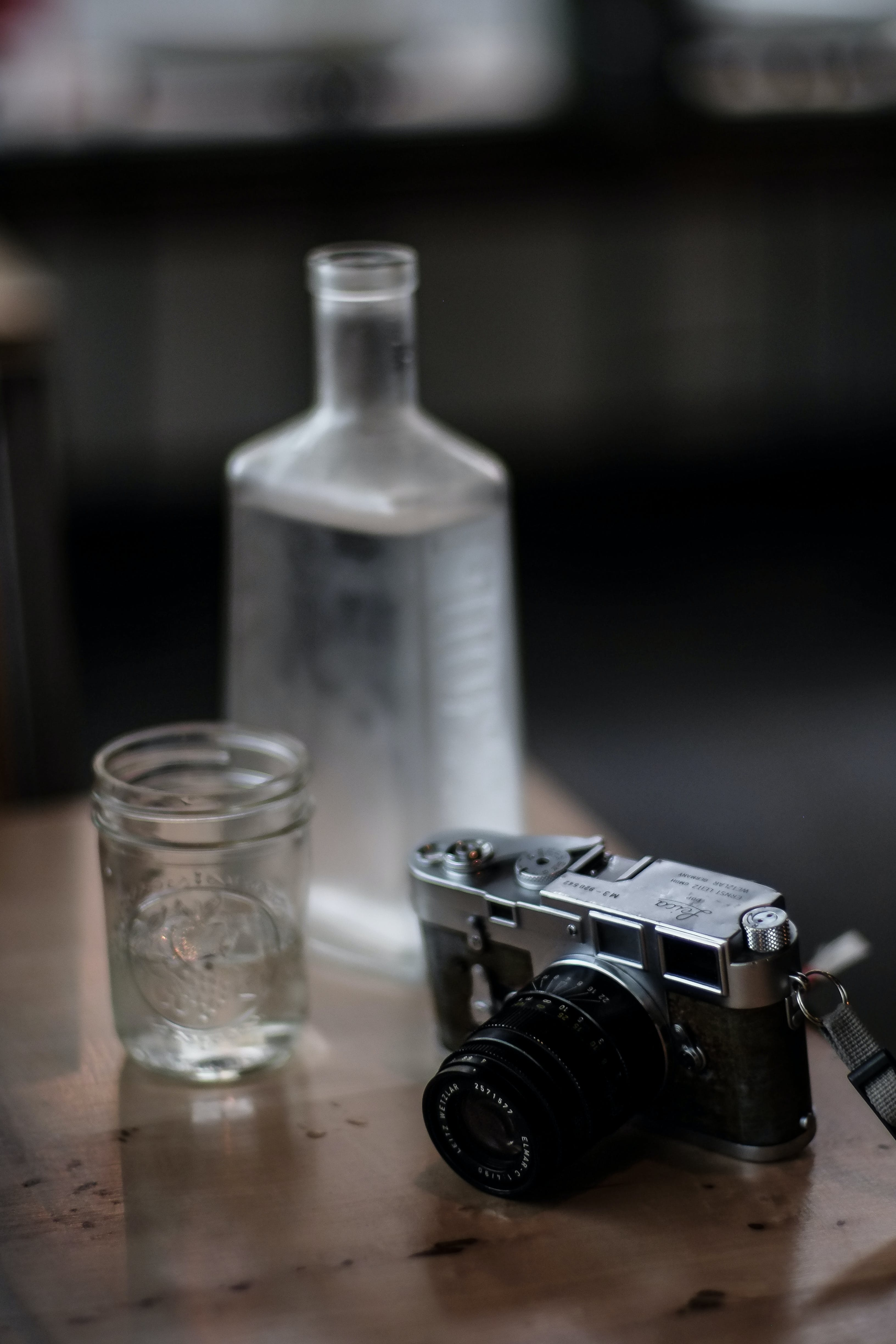 Black and Gray Camera Beside Drinking Glass