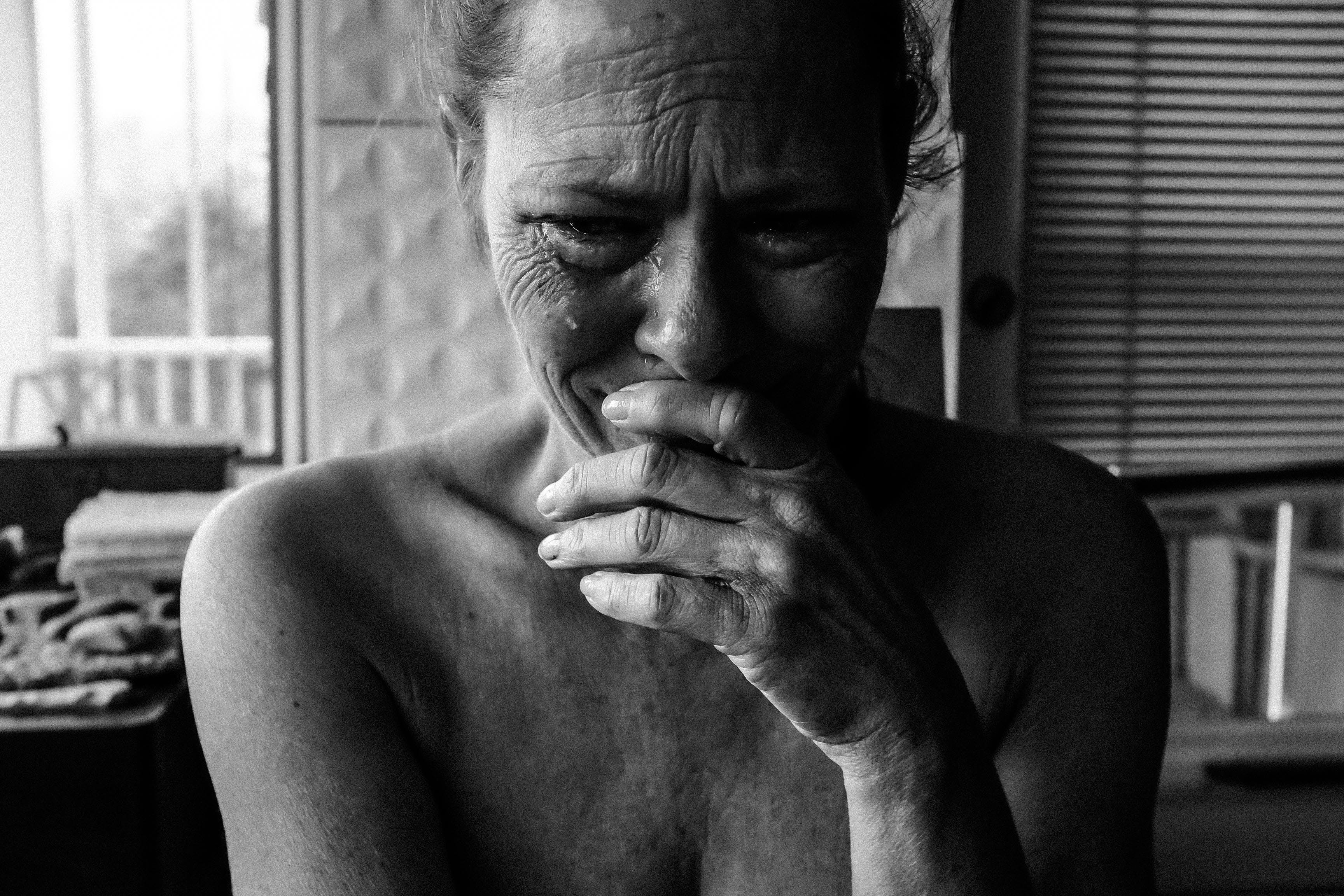 Close-up Photography of Crying Woman Next Inside Room