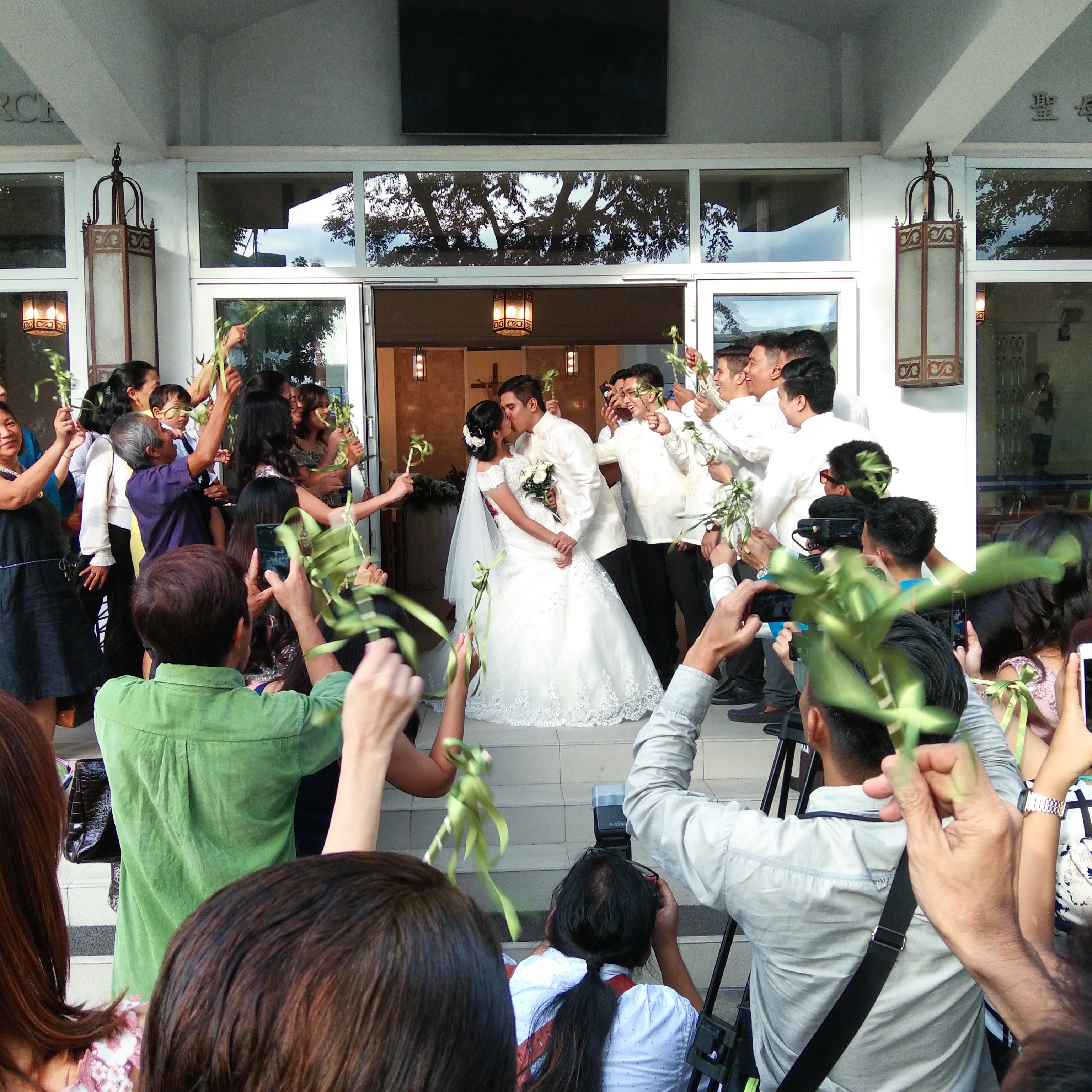 Photo of Kissing Married Couple Surrounded by Wedding Party.