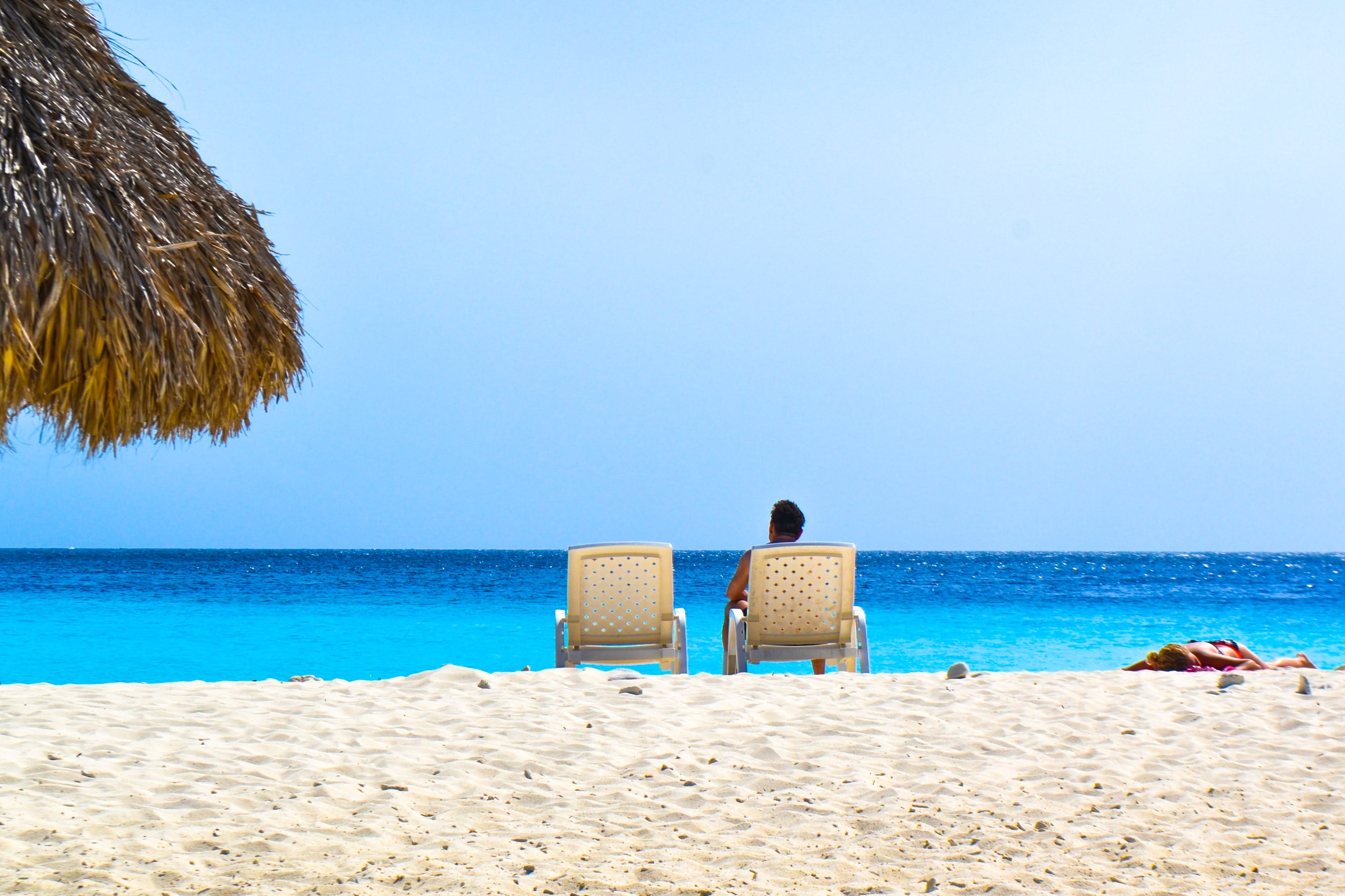 Person Sitting On Lounge Chair At The Beach