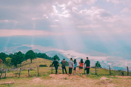 Group Of People Standing On Hill