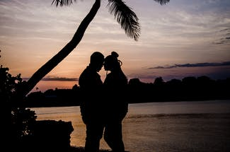 Two Person Hugging Near Tree during Sunset