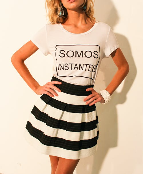 Woman Wearing White Shirt and Black and White Striped Skirt Posing