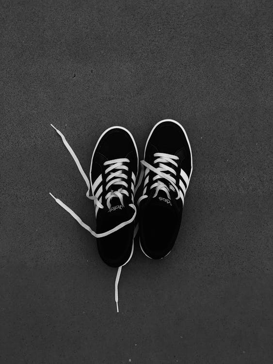 Pair of Black-and-white Adidas Sneakers on Grey Floor