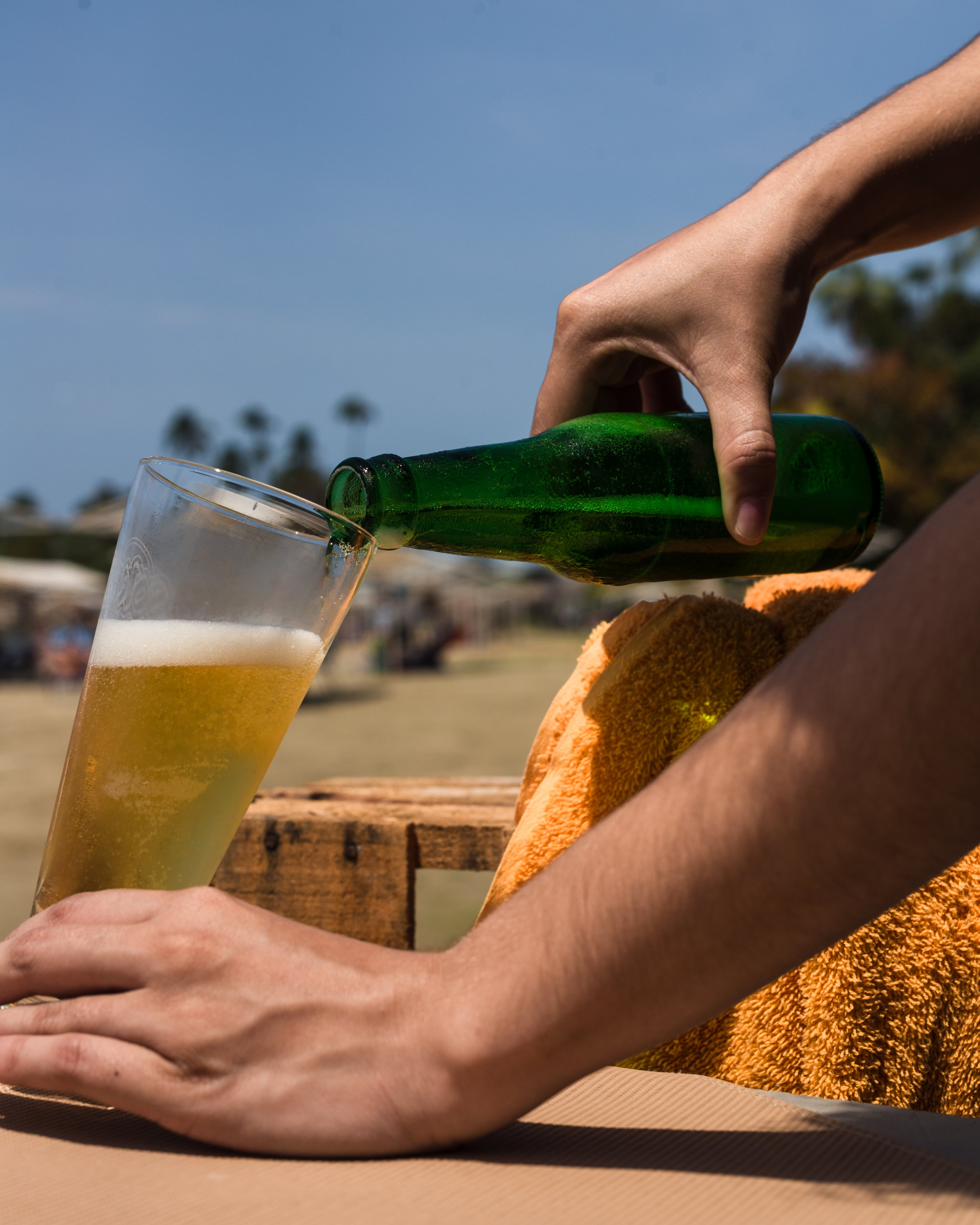 Person Holding Green Bottle Pouring Beer on Clear Glass