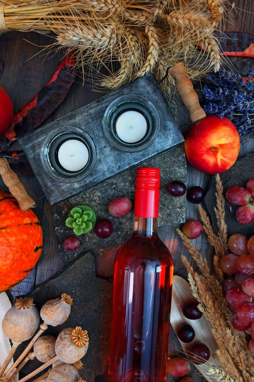 Gray Candle Holder Near Glass Bottle and Round Red Fruit on Gray Wooden Surface